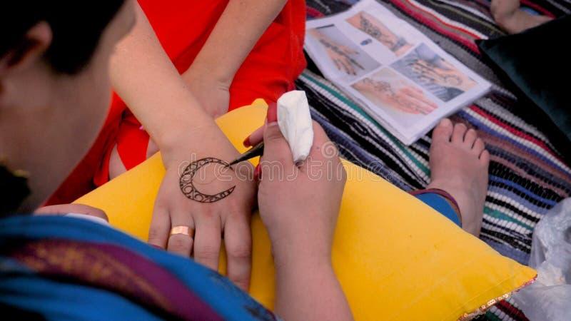 Proces om mehndi op vrouwelijke handen toe te passen De meester trekt een toenemende verf royalty-vrije stock afbeeldingen