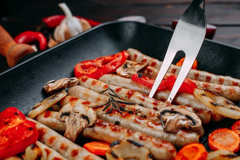Proces om smakelijke geroosterde worsten en groenten binnen te koken stock afbeelding