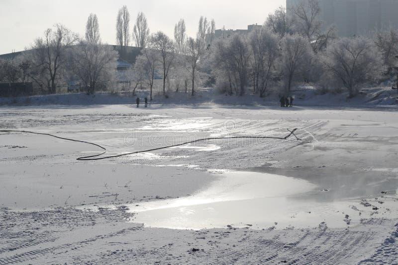 Proces przygotowywać lodowisko dla zima sezonu w mieście na mroźnym dniu fotografia stock