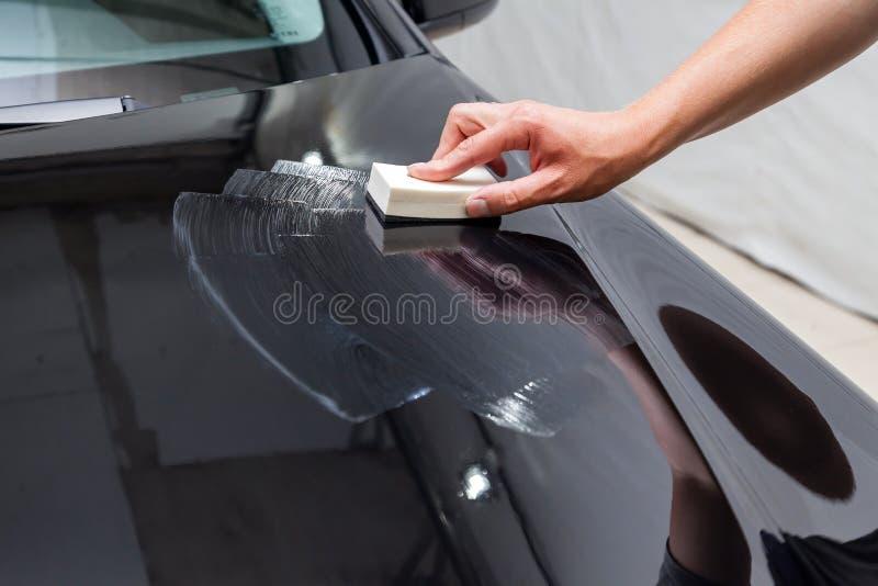 Proces stosować ceramicznego narzut na samochodu kapiszonie męskim pracownikiem z specjalnym chemicznym składem i gąbką zdjęcie royalty free