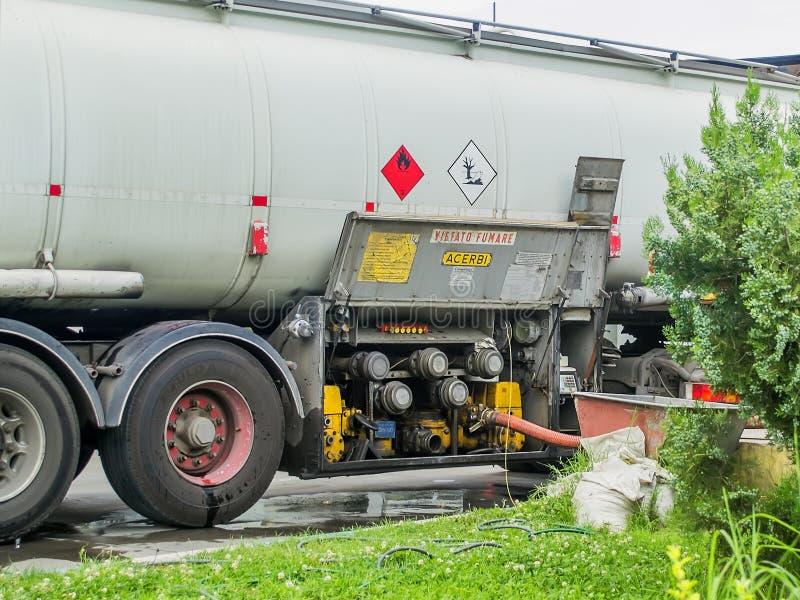 Proces van een brandstofoverdracht van een tankwagen in het reservoir van het benzinestationgas Zijaanzicht van tankspoor en verb royalty-vrije stock afbeelding