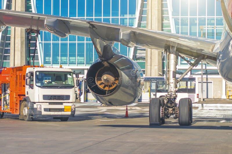 Proces van vliegtuigen het bijtanken Weergeven van de vrachtwagen, de motorvleugel en de chassis stock afbeeldingen