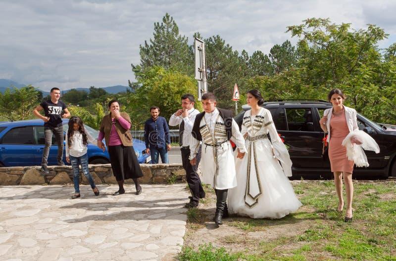 Procesión de la boda con la novia y el novio que van a divertirse en el estilo georgiano fotos de archivo