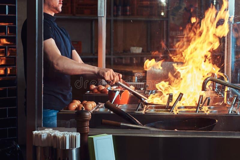 Proceso de cocinar en un restaurante asiático El cocinero es verduras de la fritada con las especias y la salsa en un wok en una  imagen de archivo