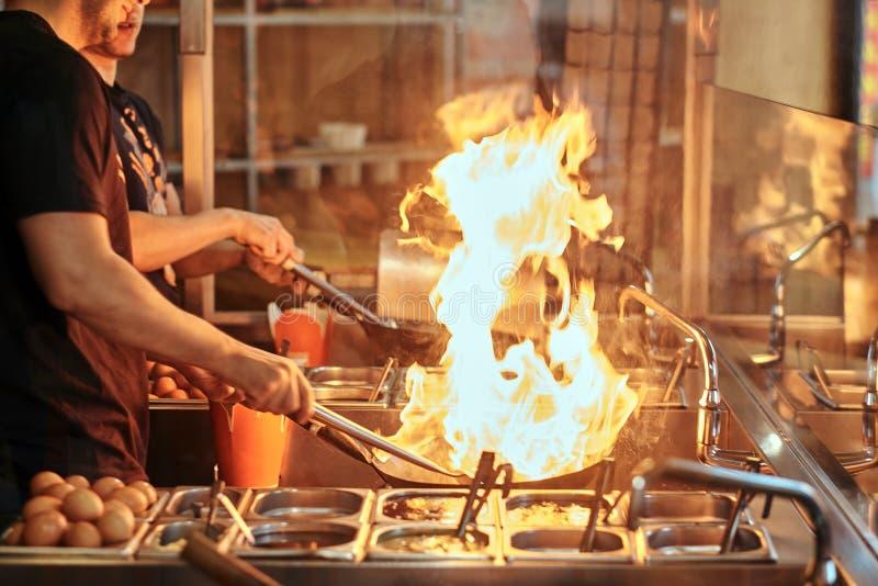 Proceso de cocinar en un restaurante asiático El cocinero es verduras de la fritada con las especias y la salsa en un wok en una  imagen de archivo libre de regalías