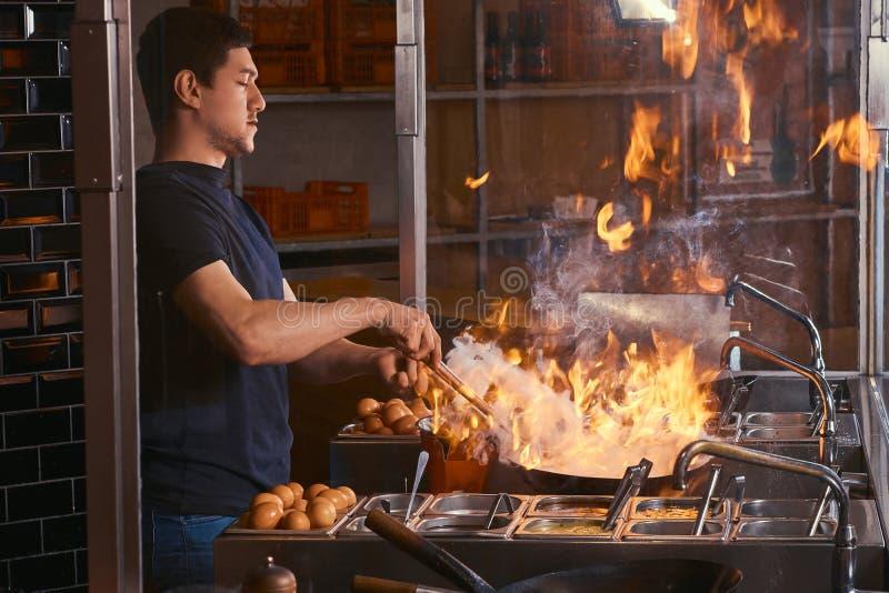 Proceso de cocinar en un restaurante asiático El cocinero es verduras de la fritada con las especias y la salsa en un wok en una  imagenes de archivo