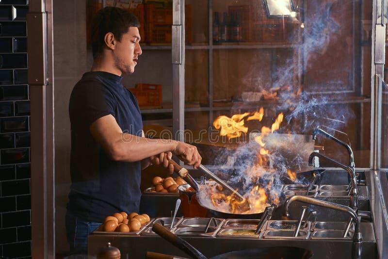 Proceso de cocinar en un restaurante asiático El cocinero es verduras de la fritada con las especias y la salsa en un wok en una  fotografía de archivo