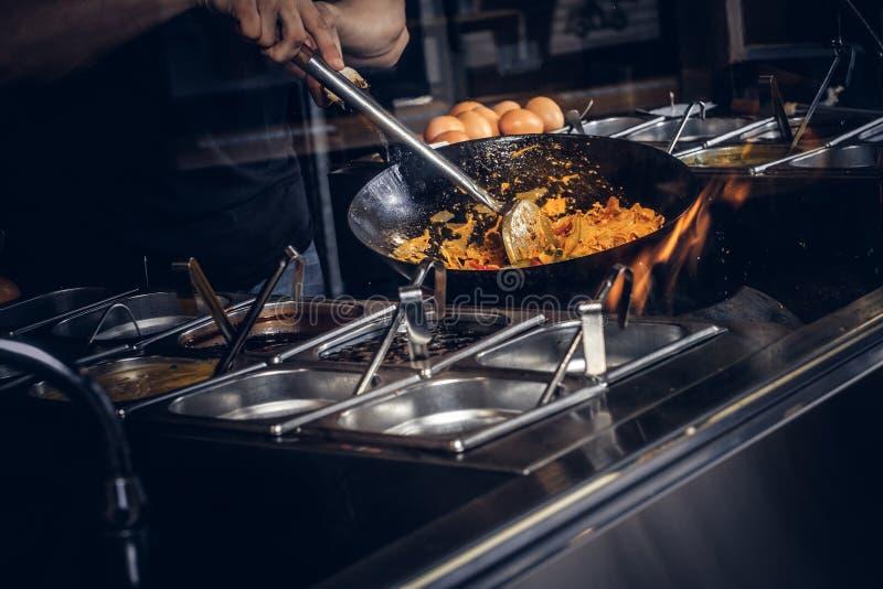 Proceso de cocinar en un restaurante asiático El cocinero está revolviendo verduras en wok fotos de archivo libres de regalías