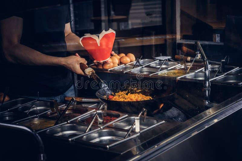 Proceso de cocinar en un restaurante asiático El cocinero está revolviendo verduras en wok imagenes de archivo