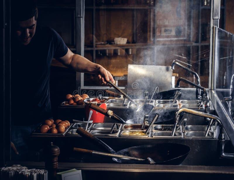 Proceso de cocinar en un restaurante asiático El cocinero está revolviendo verduras en wok foto de archivo libre de regalías