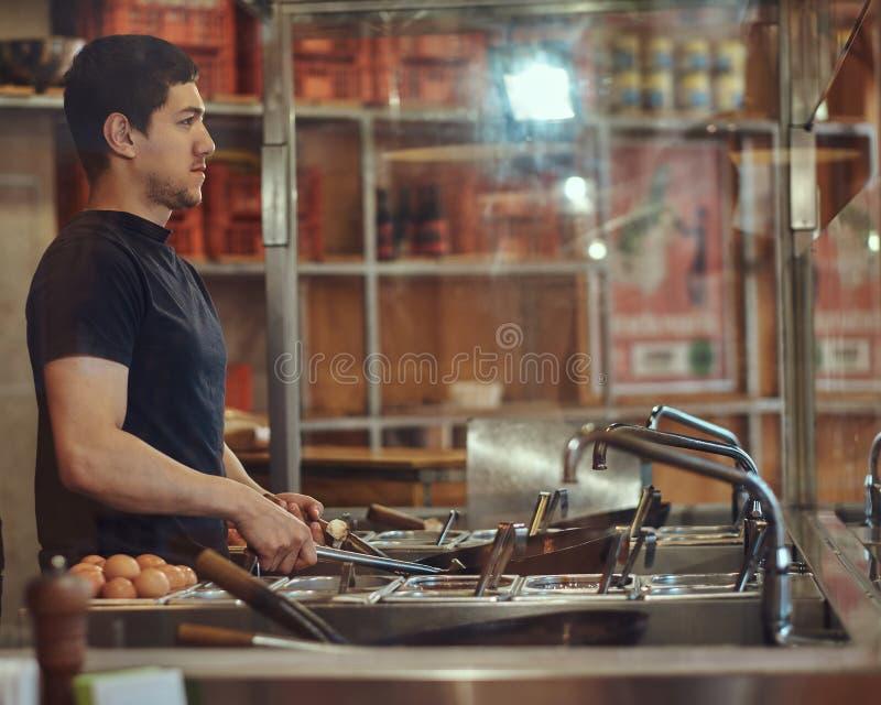 Proceso de cocinar en un restaurante asiático El cocinero está revolviendo verduras en wok foto de archivo