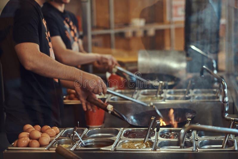 Proceso de cocinar en un restaurante asiático El cocinero está revolviendo verduras en wok fotografía de archivo