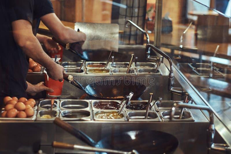 Proceso de cocinar en un restaurante asiático El cocinero está revolviendo verduras en wok fotografía de archivo libre de regalías