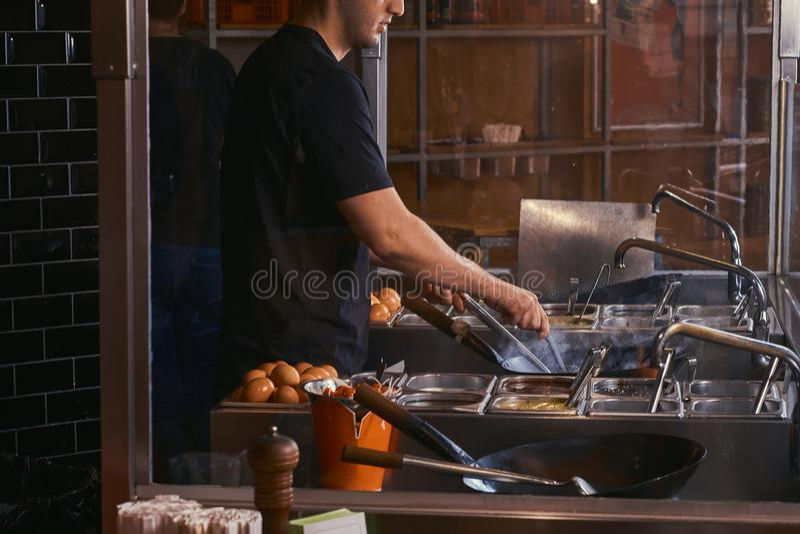 Proceso de cocinar en un restaurante asiático El cocinero está revolviendo verduras en wok imagen de archivo