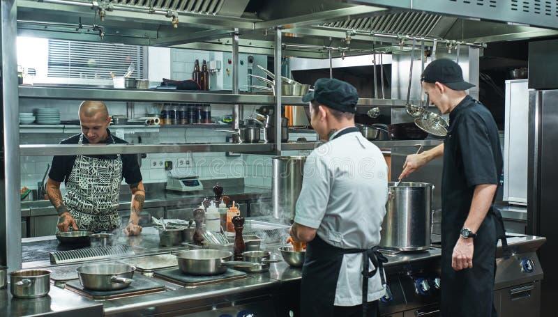 Proceso de cocinar Equipo profesional de cocinero y del ayudante joven dos que preparan la comida en una cocina del restaurante fotografía de archivo libre de regalías