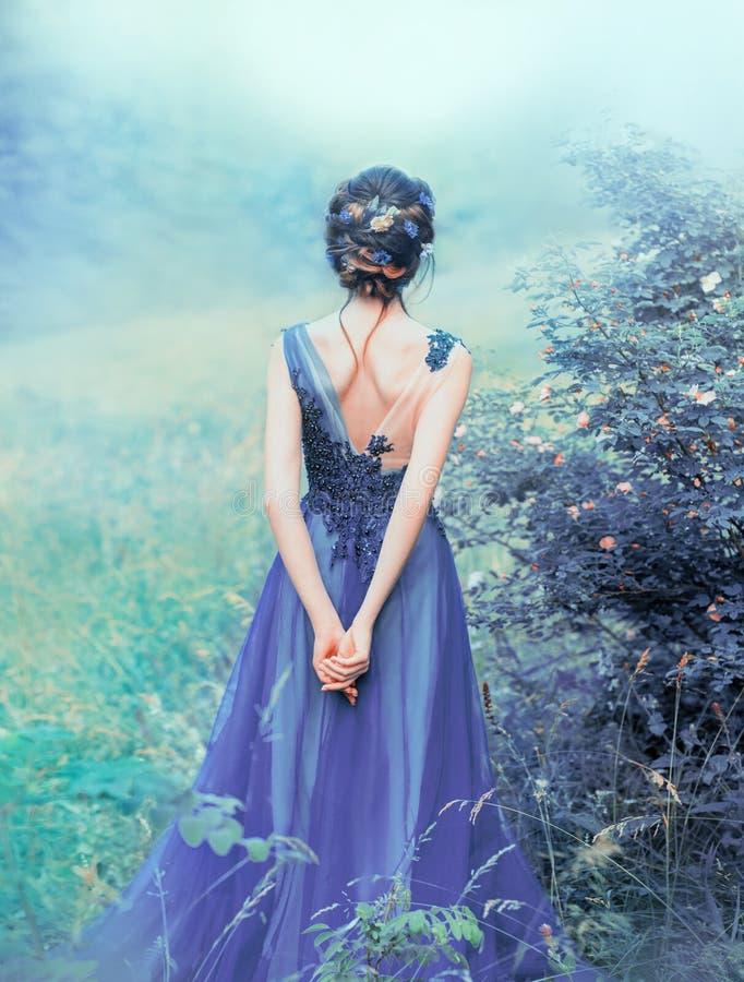 Proceso de fotos creativas con las flores frescas inusuales, muchacha dulce del arte con el pelo volado negro, flores adornadas,  foto de archivo libre de regalías