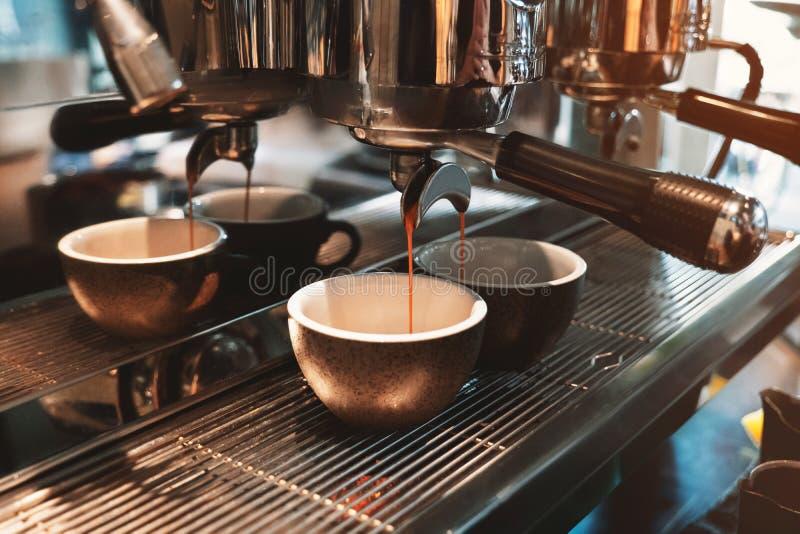 Proceso de hacer dos tazas de la bebida del café al mismo tiempo usando la máquina profesional del café en café imagenes de archivo
