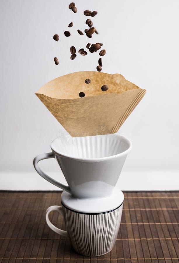 Proceso de hacer el café con las tazas, las habas y el filtro que vuelan Magia coffeemaking foto de archivo libre de regalías