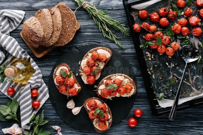 Proceso de hacer los bocadillos con la mozzarella y los tomates en la tabla de madera fotos de archivo libres de regalías