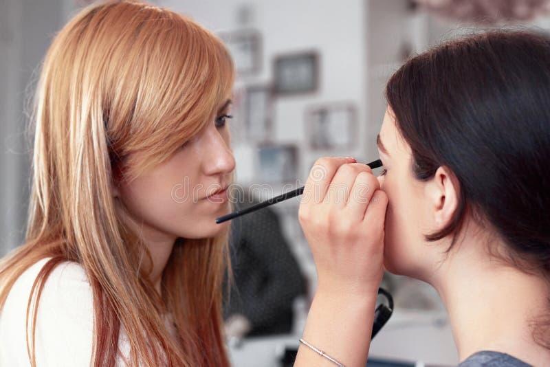 Proceso de hacer maquillaje Artista de maquillaje que trabaja con el cepillo en la cara modelo Retrato de la mujer joven en inter imagen de archivo