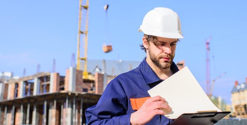 Proceso de la construcción del control del capataz Control del contratista según plan Soporte protector del casco del ingeniero d fotografía de archivo libre de regalías