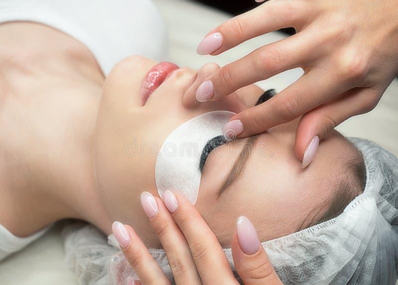 Proceso de la extensión de la pestaña Cara femenina con los ojos cerrados y los latigazos y el remiendo negros largos del algodón imagen de archivo