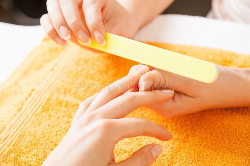 Proceso de la manicura en las manos femeninas fotografía de archivo