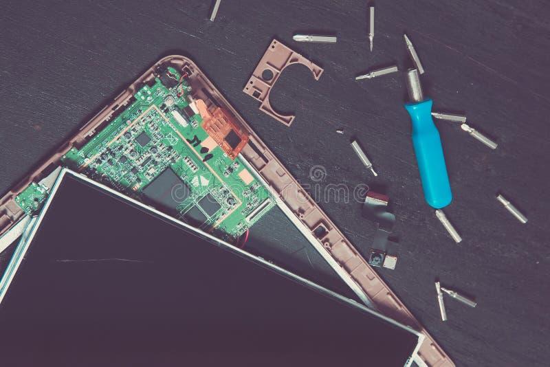 Proceso de la reparación del dispositivo de la tableta de la PC cerca del destornillador y mordida en fondo de madera negro desen imagen de archivo