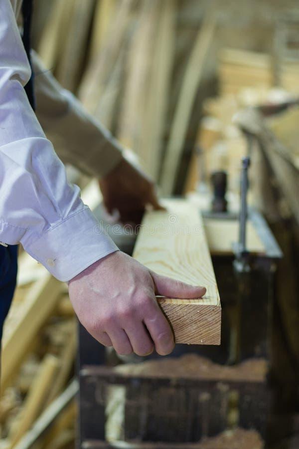 proceso de madera Carpintero de sexo masculino joven confiado que trabaja con madera en su taller fotos de archivo