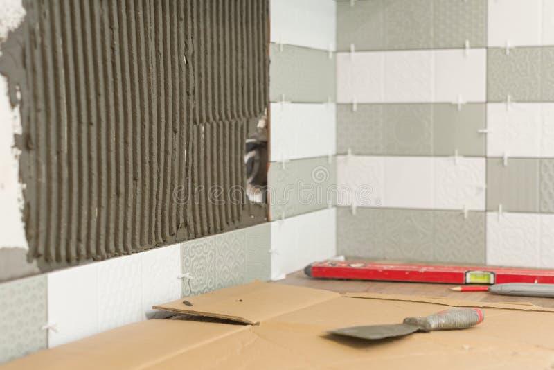 Proceso de poner las baldosas cerámicas, la construcción y la reparación en la cocina, tejas, herramientas imagen de archivo