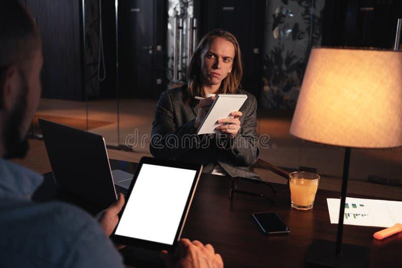 Proceso de trabajo en la oficina del desván de la noche Grupo de compañeros de trabajo jovenes que hacen la conversación sobre nu fotos de archivo libres de regalías