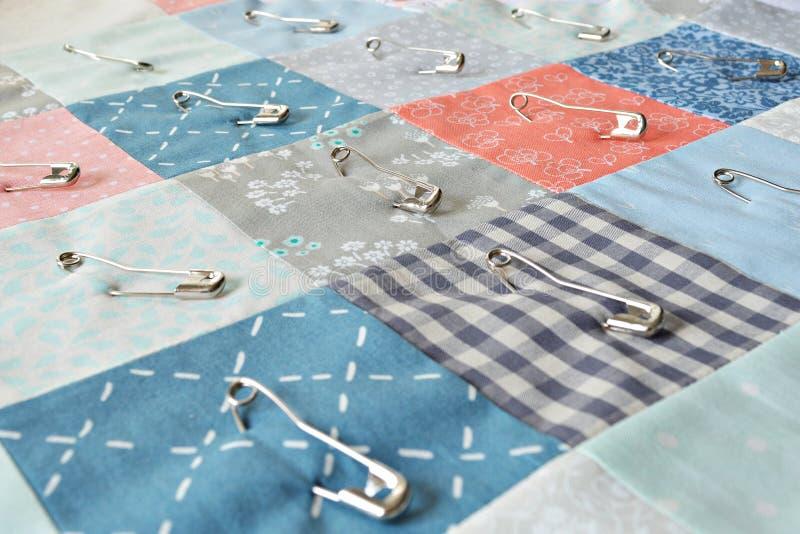 Proceso de trabajo: pedazos del algodón de la tela del remiendo y pernos de metal imagen de archivo libre de regalías