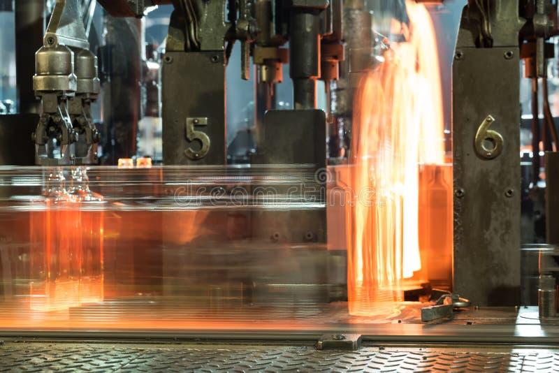 Proceso del movimiento de botellas de cristal calientes en el transportador fotos de archivo libres de regalías