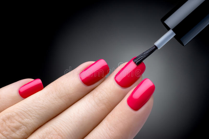 Proceso hermoso de la manicura. El esmalte de uñas que es aplicado a la mano, pulimento es un color rosado. fotos de archivo