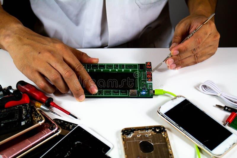 Proceso para cambiar el paso móvil 7 de las baterías para teléfono: El reparador trajo una nueva batería para comprobar la calida foto de archivo