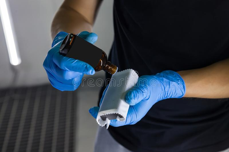 The process of applying and dripping a nano-ceramic coating on the sponge by a male worker with blue gloves and a chemical royalty free stock photos