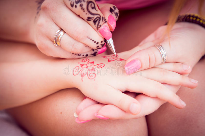 Mehndi For Children : The process of applying mehndi on children s hands close up stock