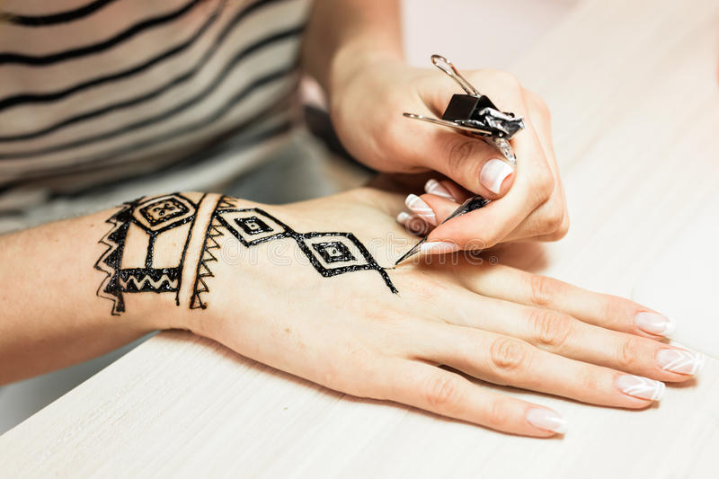 Process of applying Mehndi on female hand close up stock images