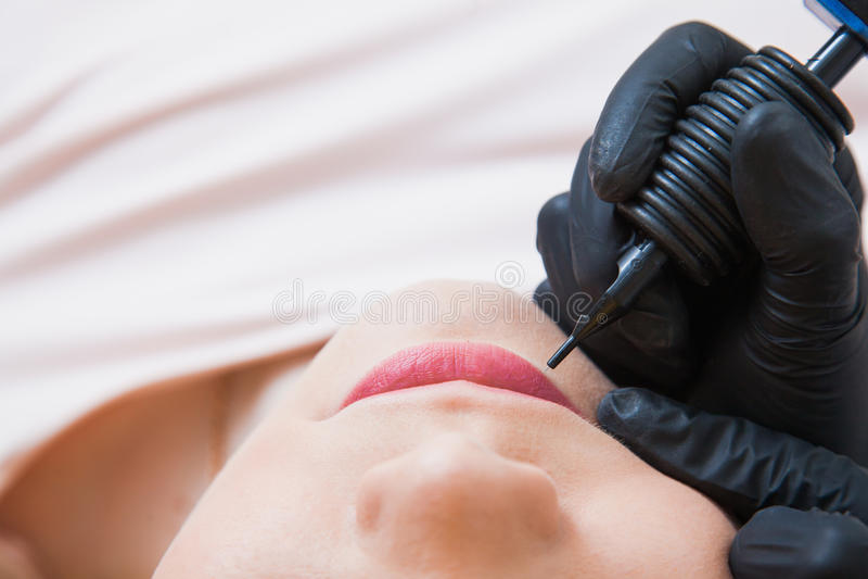 Process of applying permanent makeup tattoo pen machine stock photo