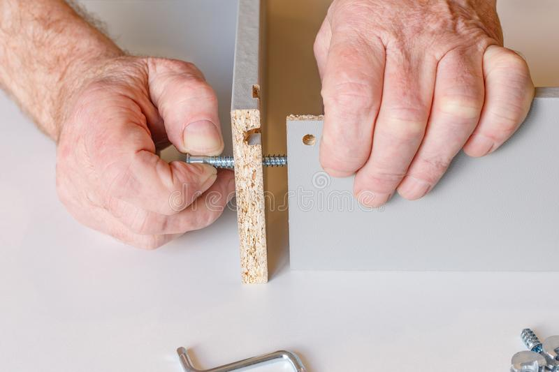 The process of assembling a kitchen box by the hands of an elderly man. Tie hex key box walls.  stock image