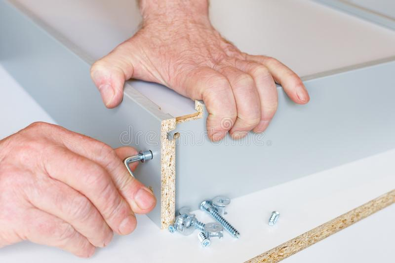 The process of assembling a kitchen box by the hands of an elderly man. Tie hex key box walls.  stock images