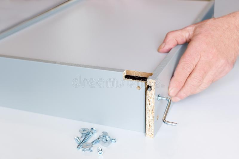 The process of assembling a kitchen box by the hands of an elderly man. Tie hex key box walls.  royalty free stock photos