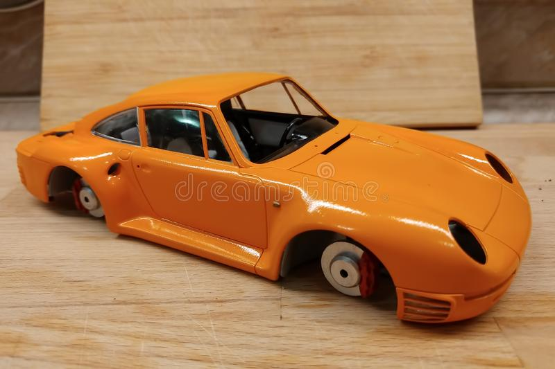 The process of assembling and painting the scale model of the car. Orange sports car in miniature stock image