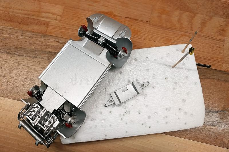 The process of assembling a scale car model. Glued and painted engine, exhaust system, suspension and brakes. Assembly part plastic kit assemble build element stock images