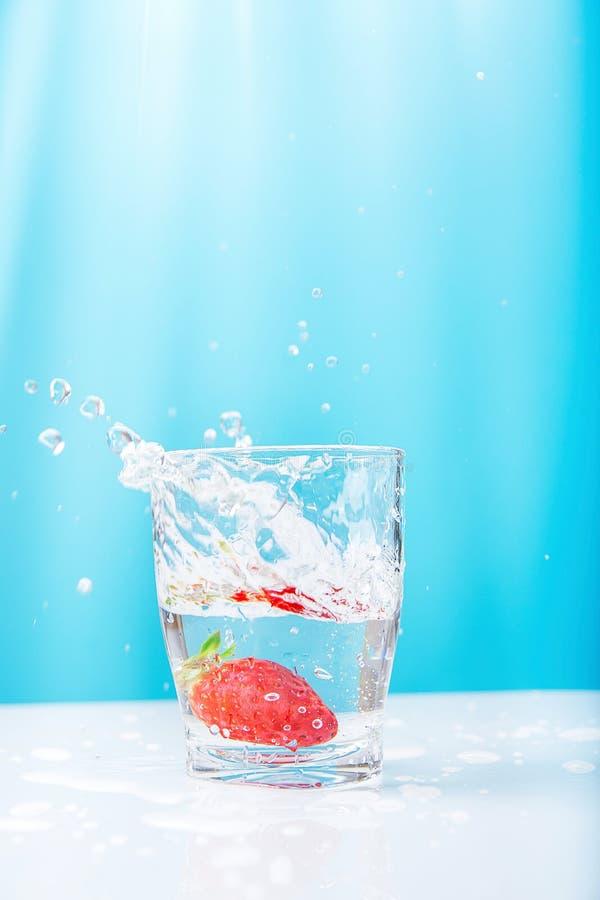 Process av att falla av den mogna saftiga sväva jordgubben in i exponeringsglas av nytt klart vatten Härliga höjdpunktfärgstänkdr arkivfoto