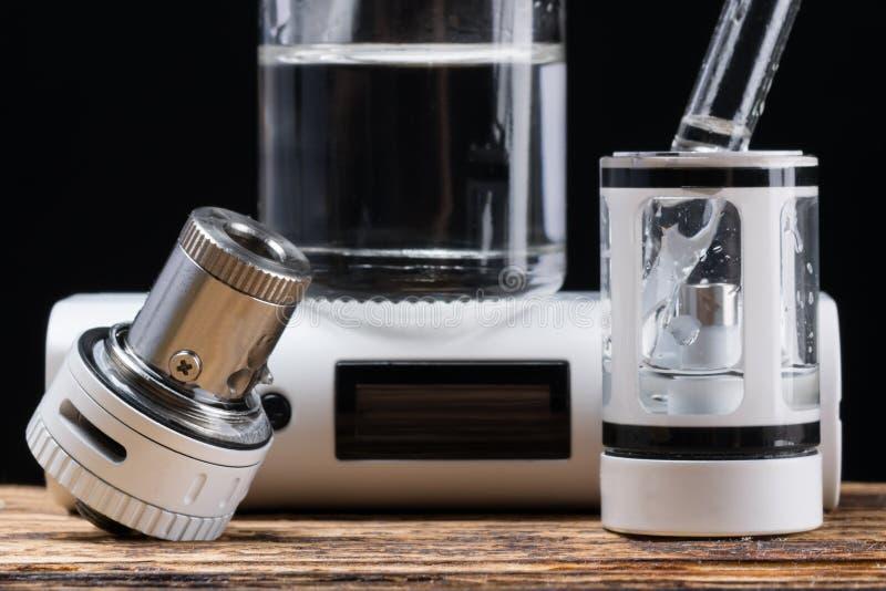 Process av att fylla en elektronisk cigarett med flytande, på skrivbordet fotografering för bildbyråer