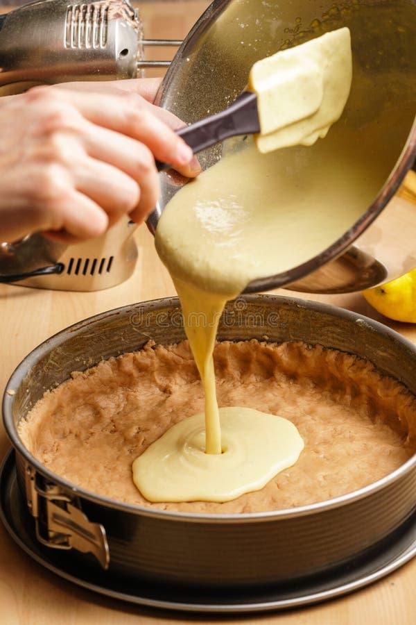 Process av att göra en läcker citronostkaka - hällande deg royaltyfri foto