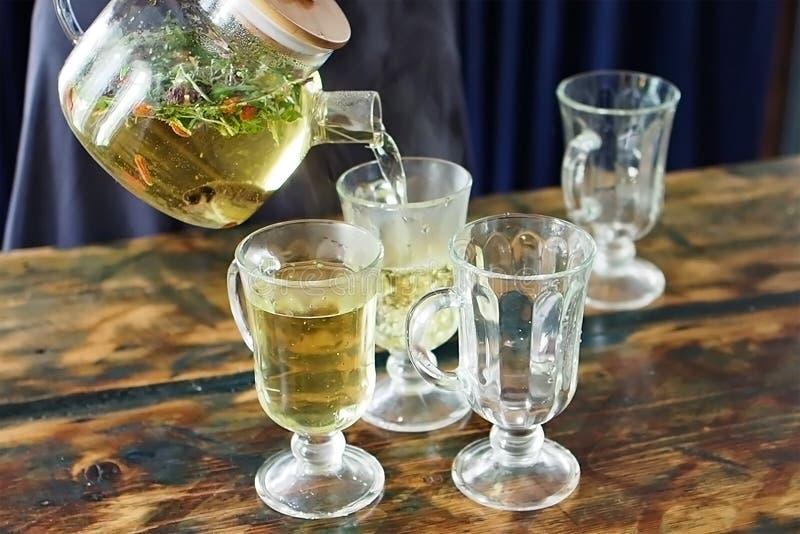Process av att hälla örtte i en genomskinlig tekanna in i härliga exponeringsglasexponeringsglas royaltyfri foto