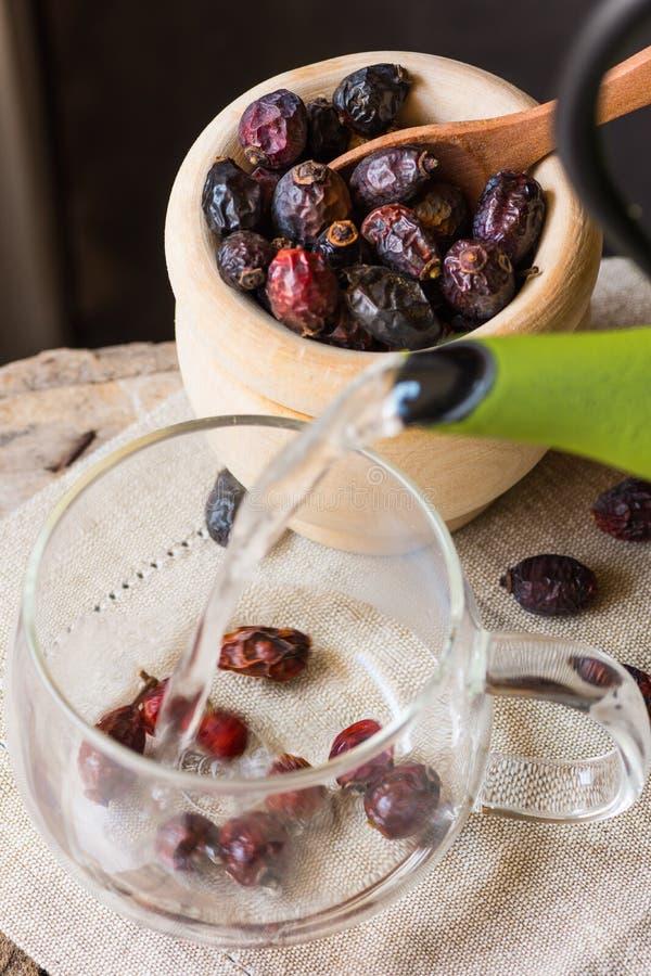 Process av att hälla varmvatten från krukan som bryggar rosa höftbär te, wood bunke, linnehandduk, hemtrevlig atmosfär fotografering för bildbyråer