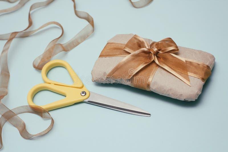 Process av att slå in gåvaasken Dekorativt papper, satängband, gul sax f?r fractalbild f?r bakgrund bl? lampa Stiliserad film fotografering för bildbyråer